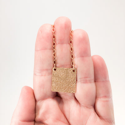 14k Gold Filled Mom's Hammer Square Necklace by Judie Raiford held in hand