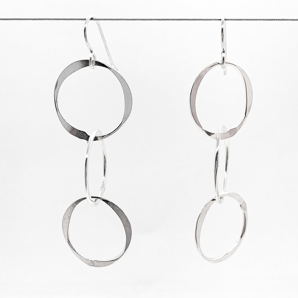 sterling silver Hammered Triple Circle Earrings by Judie Raiford hanging on a wire