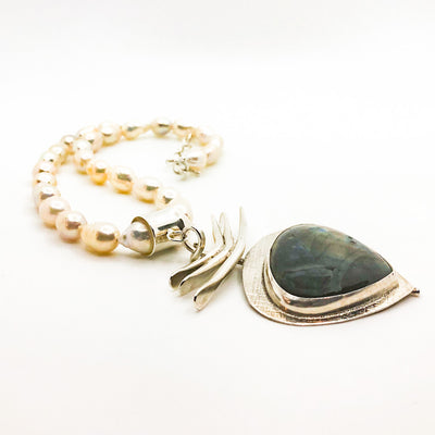 side angle view of Labradorite Pendant on 3 Blade Setting on Strand of Blush Teardrop Pearls by Judie Raiford