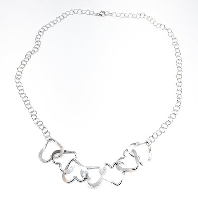 flat lay of Hammered Sterling Silver 7 Heart Necklace by Judie Raiford