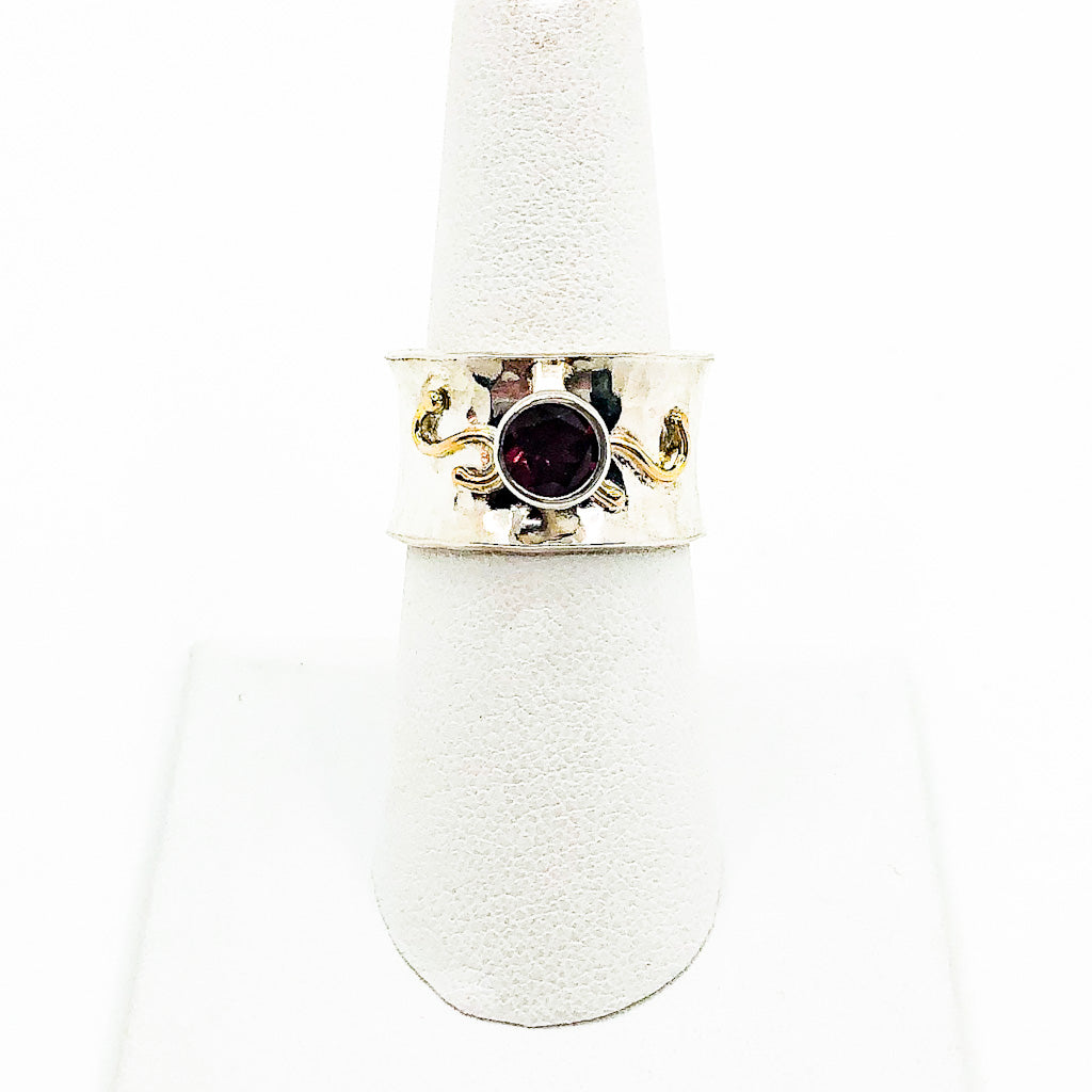 size 6 Sterling and 14k Anticlastic Ring with Rhodolite Garnet by Judie Raiford on white ring display stand