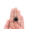 Black Onyx and 14k Gold Filled Necklace by Judie Raiford held in hand