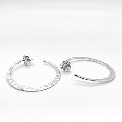 side angle view of sterling silver medium Forged Hoops by Judie Raiford