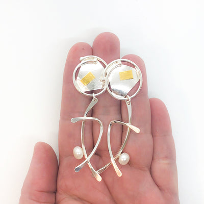 Sterling silver and 24k gold Asian Graphic Earrings with white Pearls by Judie Raiford held in hand