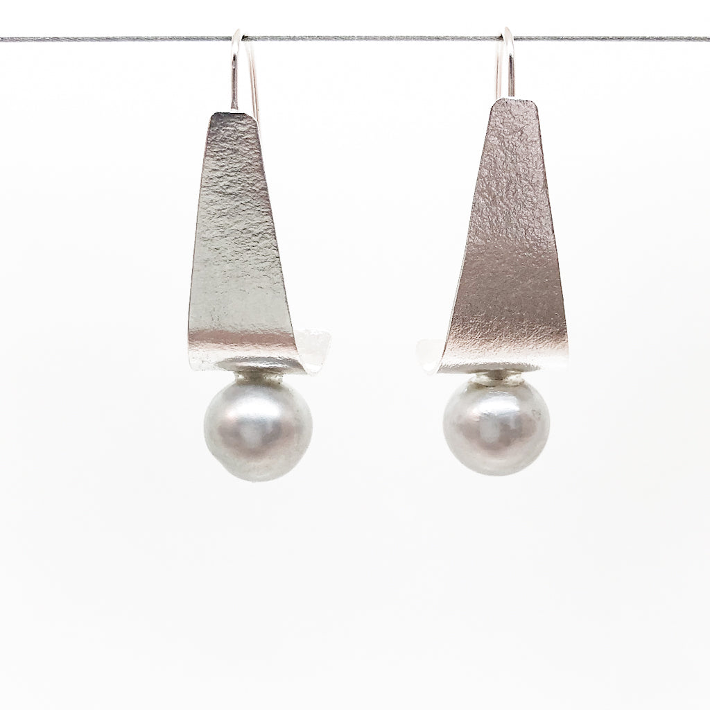 Sterling Tri Tuck Earrings with Gray Baroque Pearl by Judie Raiford hanging on a wire