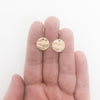 14k Gold Filled ball Pein Hammered Mini Circle Earrings by Judie Raiford held in hand