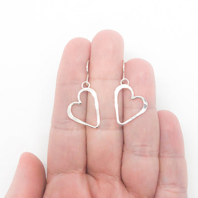 Small Sterling Silver Hammered Open Heart Earrings by Judie Raiford held in hand