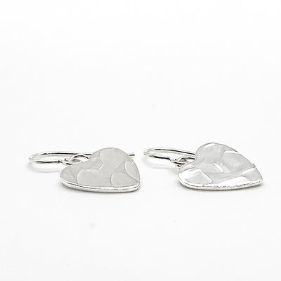 side angle view of flat lay view of Sterling Silver Small Hammered Heart Earrings by Judie Raiford