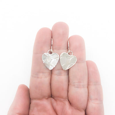 flat lay view of Sterling Silver Small Hammered Heart Earrings by Judie Raiford held in hand