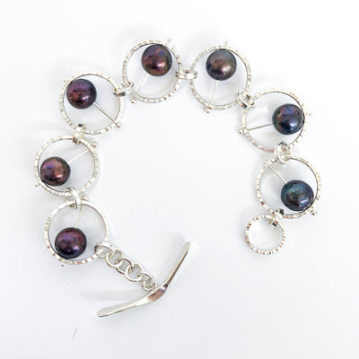 Flat Lay view of Not Naught Round Sterling Bracelet with Peacock Pearls by Judie Raiford