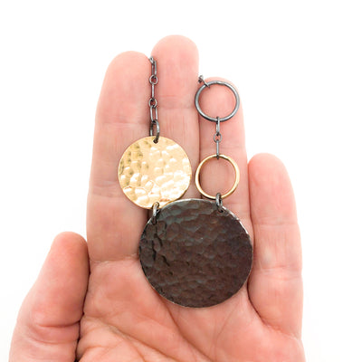 Oxidized Sterling and 14k Gold Fill Hammered Circles Necklace by Judie Raiford held in hand