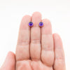 6mm Amethyst Cabochon Stud Earrings by Judie Raiford held in hand