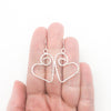 Sterling Silver Small Curly Jane Heart Textured Earrings by Judie Raiford held in hand