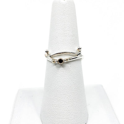 Sterling & 14k Sweet Nothing Ring with Blue Sapphire by Judie Raiford on white ring display stand