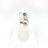 size 6.75 Sterling Wrap Ring with London Blue Topaz, Moonstone, and Peridot by Judie Raiford on white ring display stand