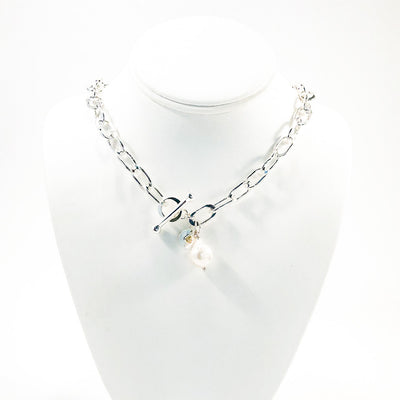 Junior Tow Truck Necklace with 14k Dangle and Large Baroque Pearl by Judie Raiford on white display mannequin