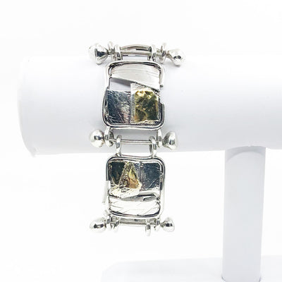 Sterling and 24k J Edgar Bracelet by Judie Raiford hanging on white bracelet display stand