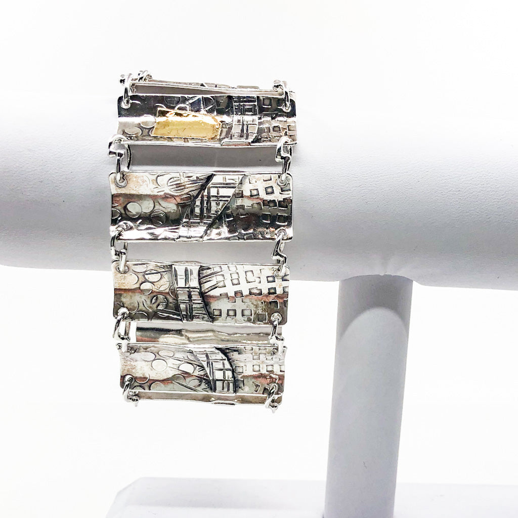 Sterling and 24k Narrow Rescue Me Bracelet by Judie Raiford on white ring display stand