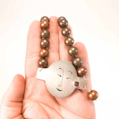 Sunstone Necklace with Bronze Pearls and Unmentionables Clasp by Ling-Yen Jones held in hand