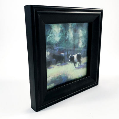 side angle view of pastel painting Black & White Cattle in black frame by Wanda Cox