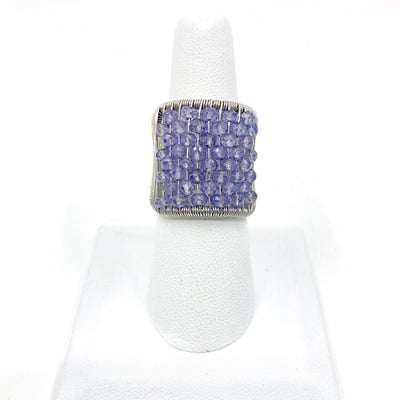 Sterling Plaited Ring with Amethyst Beads by Tana Acton on white ring display finger