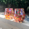 pair of Red, Gold & Silver Wine Tumblers by Nate Nardi sitting on deck hand rail with outdoor setting