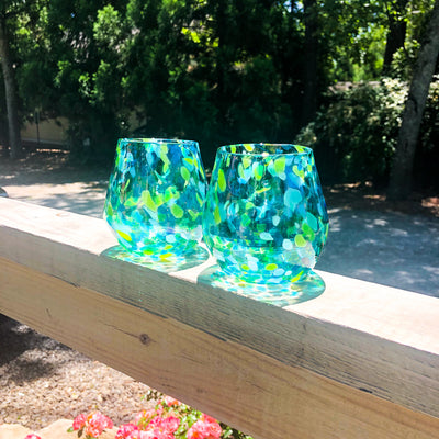 pair of Blue & Green Speckled Wine Tumblers by Nate Nardi  on deck hand rail in outdoor setting