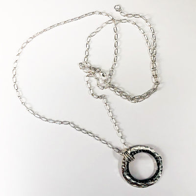 "Sterling Silver Necklace with Double Circle and Oxidized Center Circle on 30"" Sterling chain flat lay  on white background"