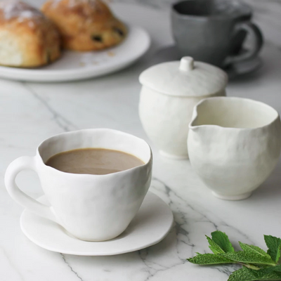 White Latte Cup and Saucer with coffee and croissants on marble counter by Nona Kelhofer