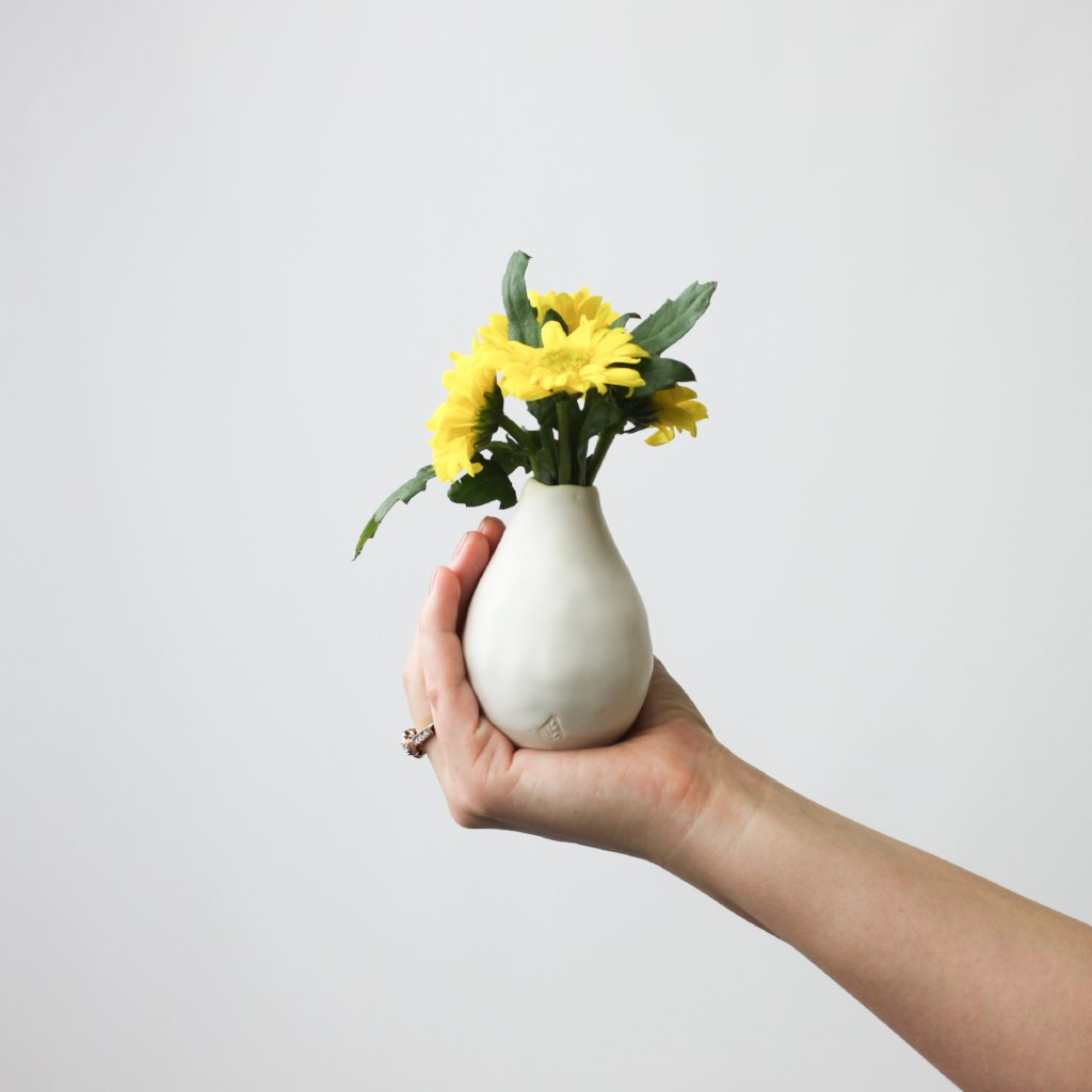 White Bud Vase by Nona Kelhofer held ih hand with yellow flowers