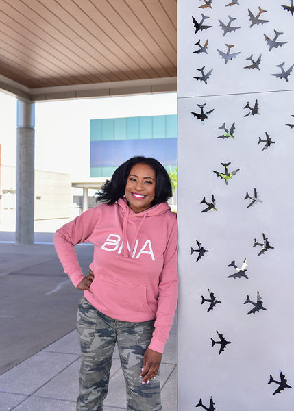 A female model wears the dusty rose BNA Logo Hoodie outside at BNA.