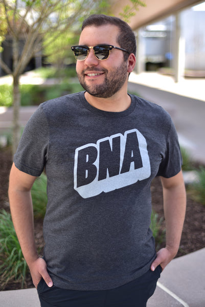 A male model wears the Upward Dark Gray T-Shirt outdoors at BNA.