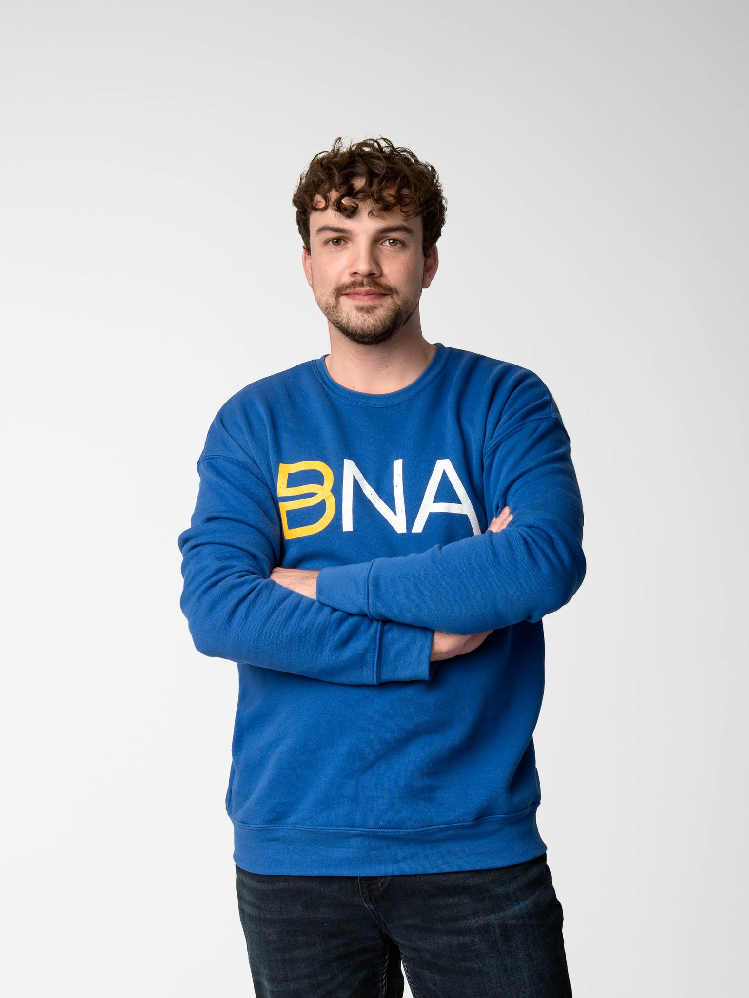 Man wearing BNA logo sweatshirt in blue