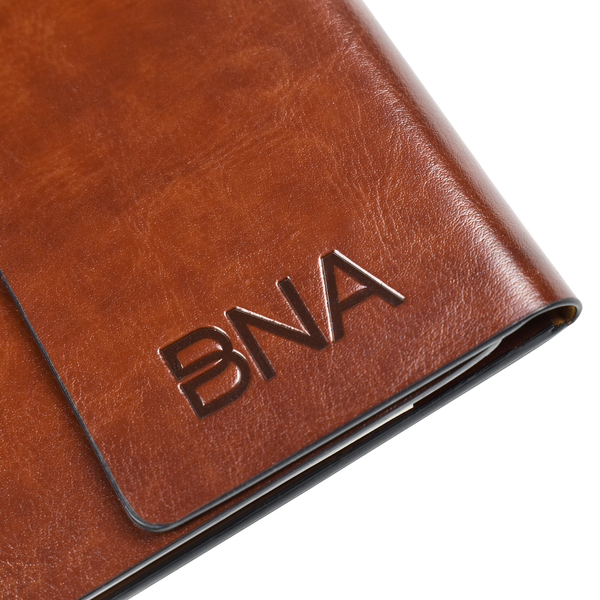 Detail shot of embossed BNA logo on cover of cognac faux leather portfolio