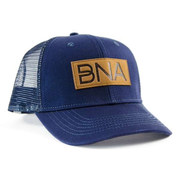 Front view of Navy BNA Patch Trucker Hat.  Navy blue hat with mesh back and sides, brown BNA logo patch.