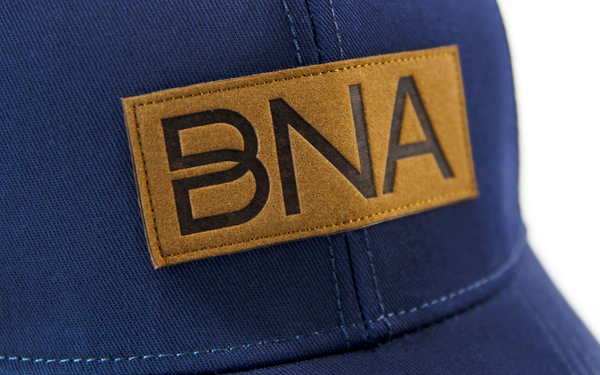 Detail view of BNA Logo patch on Navy BNA Patch Trucker Hat