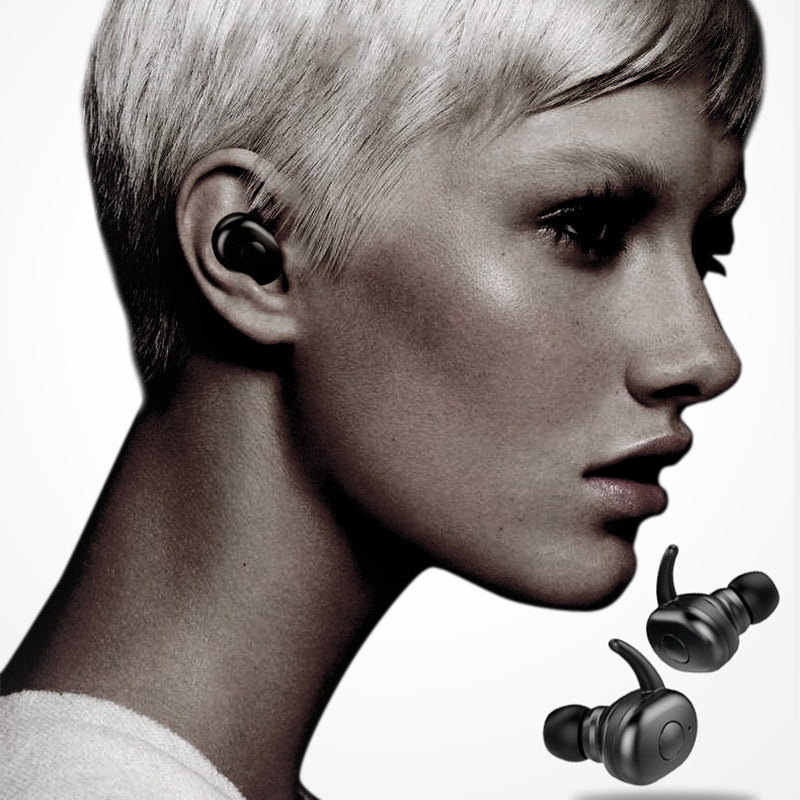 Profile of short haired blonde woman with black wireless bluetooth earbud in ear with two earbuds against white background