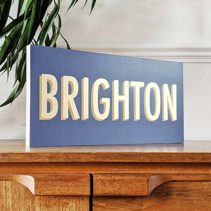 modern gold leaf inspired personalised location sign on a wooden ply block
