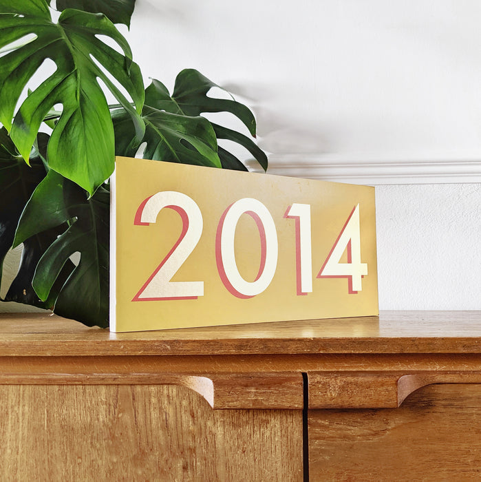 modern style gold leaf inspired personalised year sign on a wooden ply block.