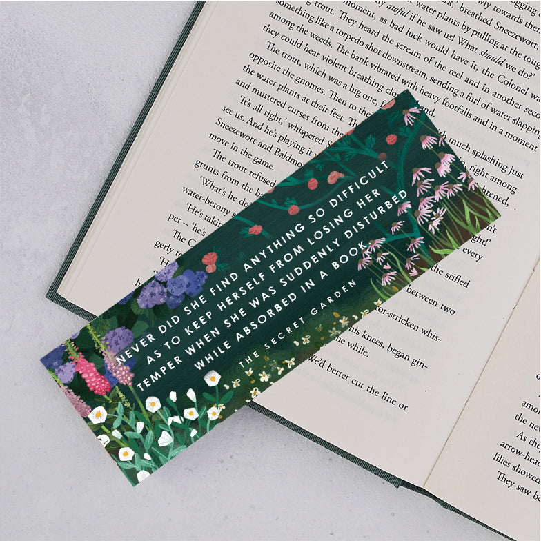 "the secret garden bookmark with floral design and green background and the following quote ""never did she find anything so difficult as to keep herself from losing her temper when we was suddenly disturbed while absorbed in a book"""