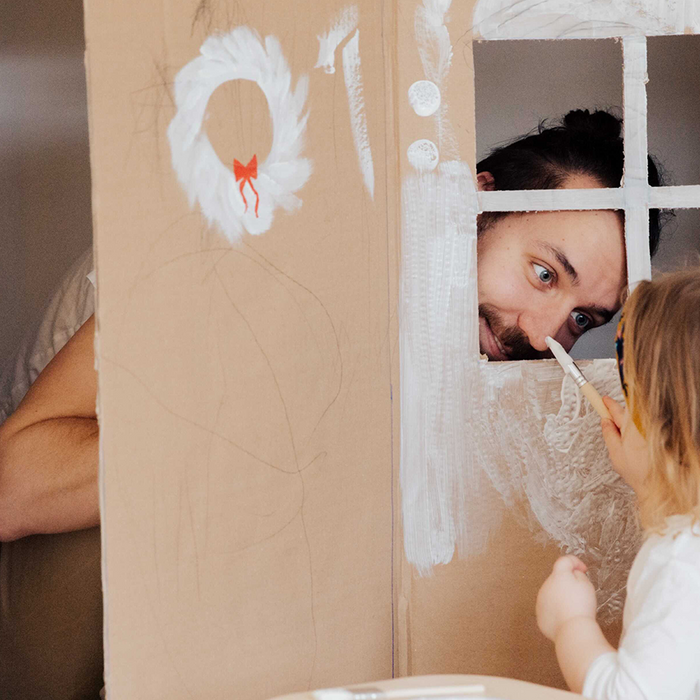 A father plays with his child through a window made of cardboard boxes