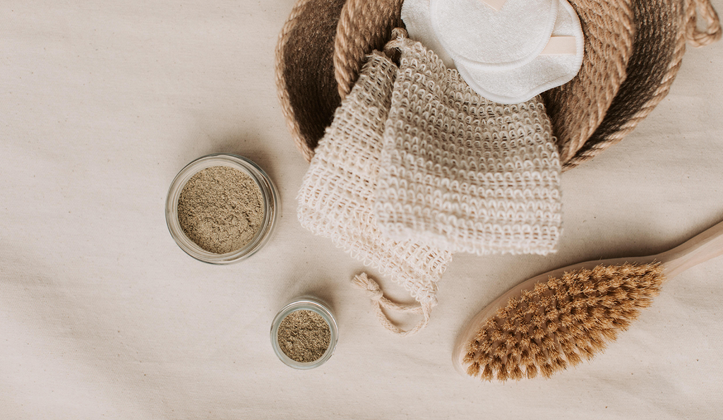 A dry brush on a linen cloth with some knit bags and jars of powder.