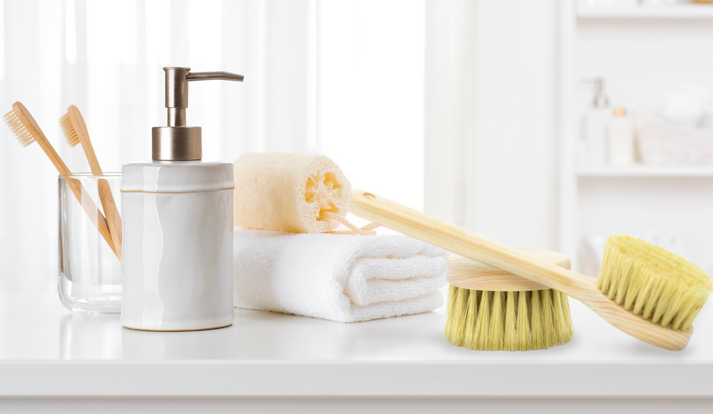 Dry brushes on a counter with a soap dispenser, tooth brushes, a folded towl, and a loofah.
