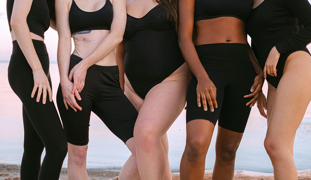 A group of women wearing black bodysuits and bathing suits
