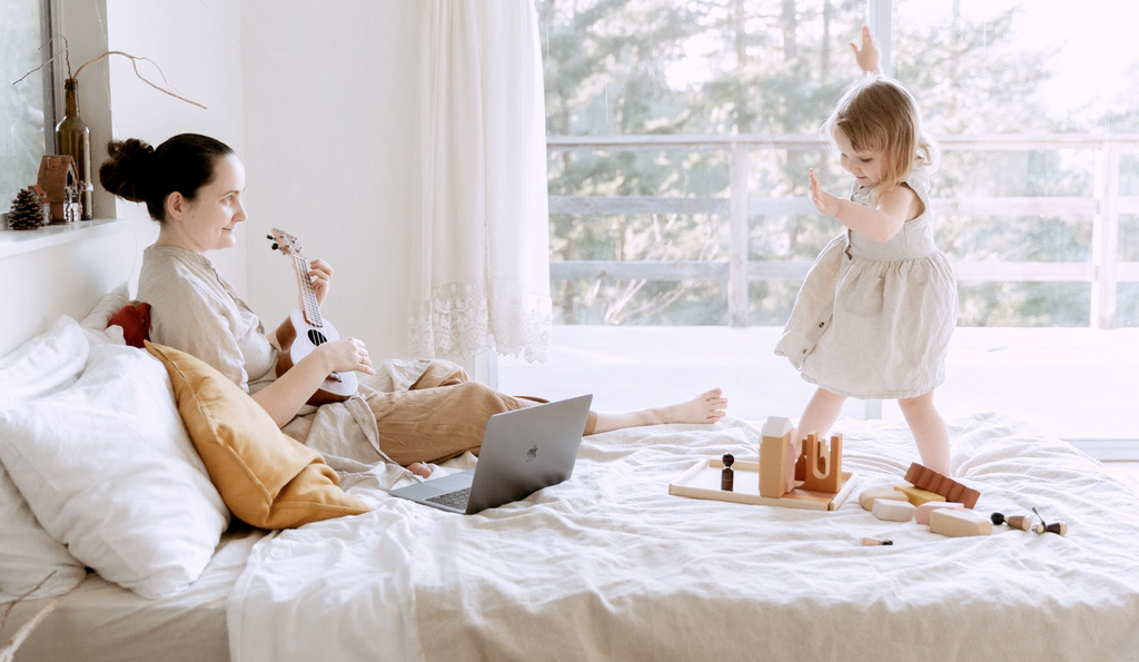A mother and child play with toys and dance to music on a bed