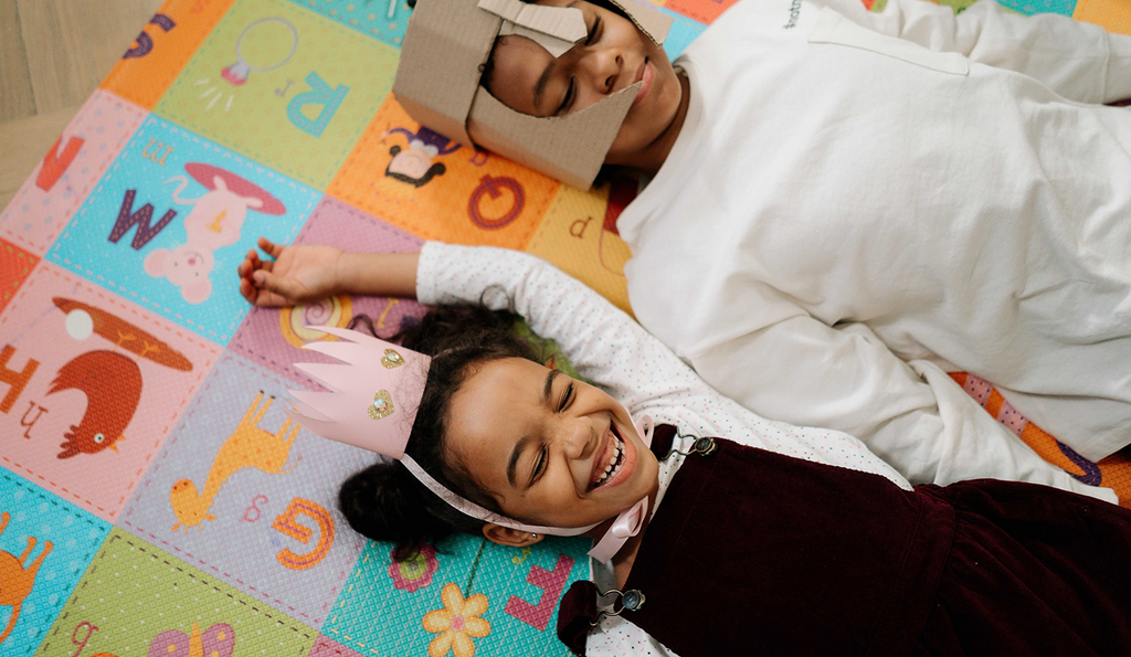 Two children smile and laugh while laying on a colourful blanket.