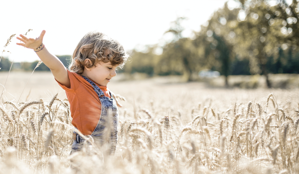 A child frolicks through a field of dry grass