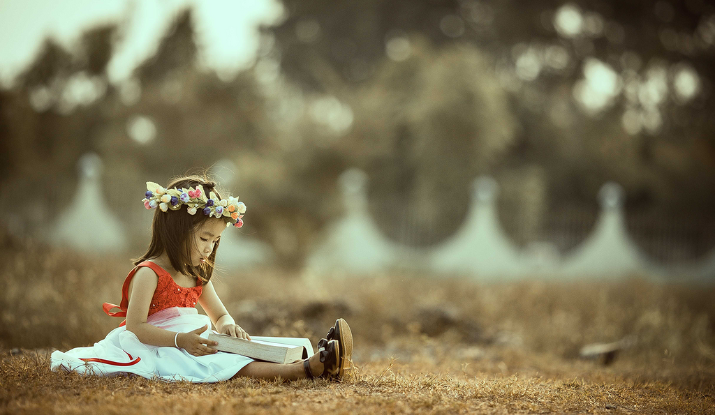 A child in a flower crown reads a book while sitting on the ground outside.