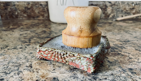 Wooden scouring dish brush in soapy water