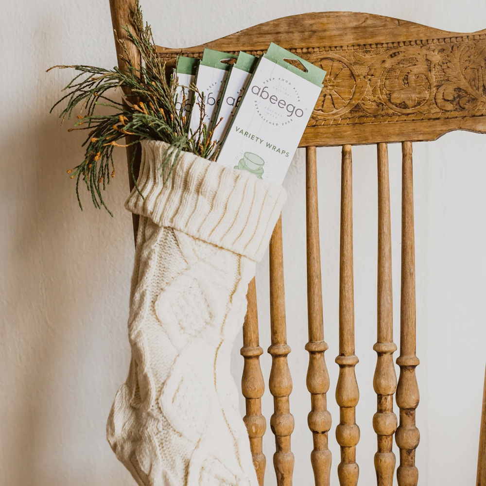 Abeego Variety Wraps boxes in a white cable-knit stocking hanging off of a wooden chair.